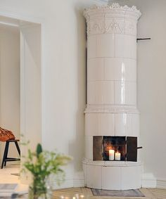 Scandinavian fireplaces could be described as simple and chic. Typical Swedish fireplaces usually resemble a column. The shape is very simple. It's basically a round chimney pipe and it's usually white. The furnace always presents two small folding doors and the top of the fireplace almost always features a crown, in the spirit of the Scandinavian monarchies traditions.