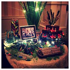 Groom's table hunting theme- black tablecloth, burlap topper, fishing net, moss, cattails, empty shotgun shells, vintage fishing lures, live fish, hand carved bowl holding cookie sticks, tree trunk cake pedestal, floral lights, duck deco, antlers, photo of groom hunting- spectator!