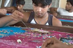 """Young men sew beads and sequins in intricate patterns onto saris and shawls at a """"zari"""" workshop in Mumbai, India. The boys, who arrive by train from impoverished villages across India, often work from six in the morning until two in the morning the next day. Some sleep on the floor of the workshop. If they make the smallest mistake, they might be beaten. All say they work to send money back to their families, but some employers are known to withhold their meager pay."""