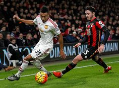 Manchester United's English midfielder Jesse Lingard vies with Bournemouth's English defender Adam Smith during the English Premier League football...