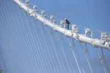 A bridge worker walks up a cable of the newly constructed San Francisco-Oakland Bay Bridge on July 12, 2013 in Oakland, California - Photo by Justin Sullivan / Getty Images News / Getty Images
