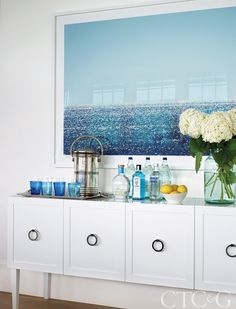 The water theme continues with a seaside photograph by Renate Aller hanging above a lacquered console that serves as a bar.