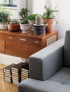 Vasos com plantas e livros ressaltam um dos móveis favoritos da proprietária, esta rádio-vitrola. O toque contemporâneo vem do sofá (Bó Jeito de Morar) de linho e com traços retos.