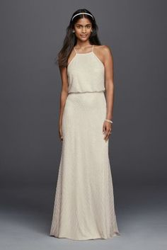 Great for that destination or beach wedding of your dreams! This blouson halter style sheath wedding dress compliments everyone with it's fun and flirty design. The all-over beaded detailing and floor length flowing skirt