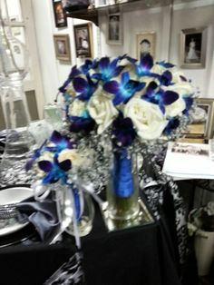 white roses blue orchids wrapped in royal blue