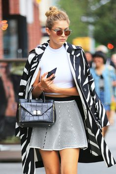 Gigi Hadid in a white crop top and textured skater skirt, topped with a zebra print coat and colored lens sunglasses