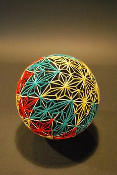 "てまり (""hand ball"" in Japanese) is a folk craft born in ancient Japan from the desire to amuse and entertain children with an embroidered toy thread ball."
