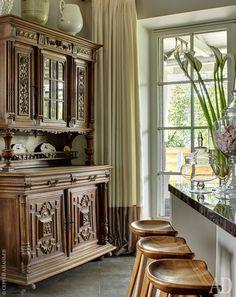 Заказчик с самого начала мечтал о старинном буфете. Его купили в Санкт-Петербурге. У кухонного острова — стулья Tractor Counter Stool по дизайну Крейга Бассама.