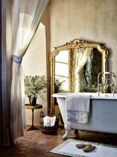 Love the claw foot tub and the ornate floor mirror. Transforms this little space into a luxurious-feeling space