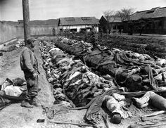 Bodies of some 400 Korean civilians lie in and around trenches in Taejon's prison yard during the Korean War in September 1950. The victims were bound and slain by retreating Communist forces before the 24th U.S. Division troops recaptured the city Sept. 28. Witnesses said that the prisoners were forced to dig their own trench graves before the slaughter. Looking on, at left, is Gordon Gammack, war correspondent of the Des Moines Register and Tribune. (AP Photo/James Pringle)