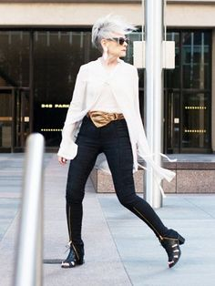 Lyn Slater of Accidental Icon wears a white blouse, gold belt, skinny trousers, statement earrings, and peep-toe booties