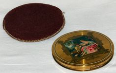 Vintage 'Le Rage' round brass powder compact with felt sleeve.