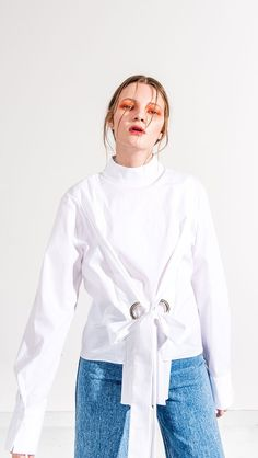 The Sibi top with eyelet tie front and low turtleneck collar. Concealed zip closure at back. Pull on. COMPOSITION AND CARE Dry Clean Please treat with care to extend the life of your cloth 100% Cotton