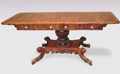 An unusual early 19th Century Regency period figured mahogany Sofa Table having rosewood, maple, boxwood & ebony crossbanded top above angled frieze drawers raised on boldly carved & fluted centre pedestal with shell-carved platform base ending on scrolled legs with hairy carving retaining original brass lion's paw castors. Circa: 1830