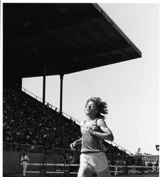 Black and white photo of an unidentified female University of Oregon runner in stride during a 1981 race held at Hayward Field. ©University of Oregon Libraries - Special Collections and University Archives