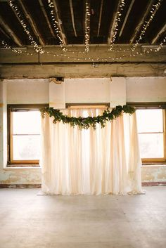 Photographer: Something Gold Photography; Chic wedding ceremony with green garland hanging across;