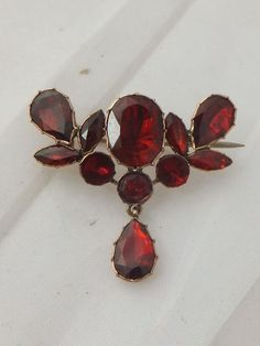 Fine Georgian Garnet gold,unmarked but fully tested, brooch/pendant. The largest Garnet being carat graduating down 20 points, all of beautiful colour. The brooch measures x grammes. Garnet Jewelry, Gold Jewelry, Fine Jewelry, Gemstone Brooch, Garnet Gemstone, Diamond Brooch, Victorian Jewelry, Antique Jewelry, Vintage Jewelry