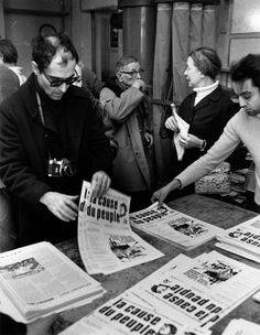Jean-Luc Godard, Jean-Paul Sartre, and Simone de Beauvoirgather to distribute copies of the Maoist newspaper La Cause du Peuple on the street after it is banned by the government (Paris, 1970).    Photographer: Bruno Barbey.