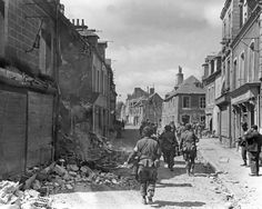 American troops walk down the streets of Carentan - a port city in Normandy - for which US airborne forces fiercely battled the German Wehrmact in 10 - 11 June, 1944. A lack of ammunition forced the German forces to withdraw on 12 June. The 17th SS PzG Division counter-attacked the 101st Airborne on 13 June. Initially successful, its attack was thrown back by Combat Command A (CCA) of the U.S. 2nd Armored Division.