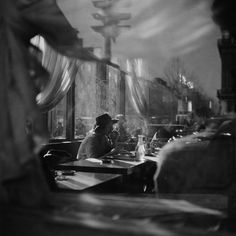 Ernst Haas – A woman drinking at a table in a Paris cafe., 1950