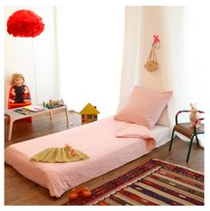 Mattress on the floor for a Montessori-inspired room. I like the simple curtain-as-headboard idea.