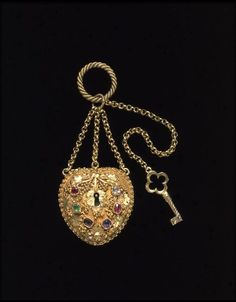 A heart locked with a key, and a secret message: the colored stones have initial letters that spell 'REGARD': ruby, emerald, garnet, amethyst, ruby and diamond. This arrangement of stones was also popular in 'regard' rings. The pendant opens to reveal a panel of woven hair under glass. ca.1840, from the Victoria and Albert Museum.