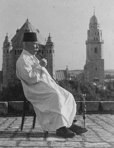 An Armenian priest in Jerusalem c. 1900 pictured smoking a hookah with the Dormition Abbey in the background