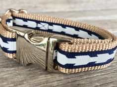 Bold white arrows on 3/8 navy colored grosgrain ribbon sewn onto a 5/8 tan, 100% nylon webbing. Collar has all silver colored metal hardware, including a side release buckle, welded steel d ring and metal triglide. All of our collars have been triple stitched at all major stress points for the safety of your dog. **COLLAR SIZES** EXTRA SMALL- adjustable 8-12 in length and 5/8 wide SMALL- adjustable 10-15 in length and 5/8 wide. MEDIUM- adjustable 13-19 in length and 5&#x2F...