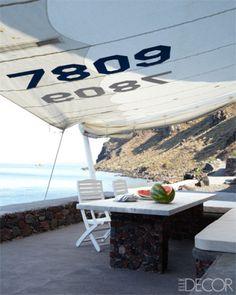 On the Greek island of Santorini, a sail provides shade on a terrace.