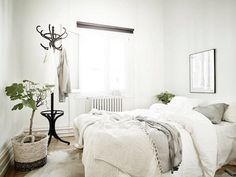 Classic black coat stand in the corner of the bedroom in a Swedish space in neutrals. . Stadshem.