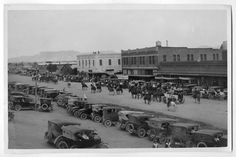 """Photograph of a rodeo parade in Alpine, Texas in October, 1924. There are several parked cars in the foreground. On the street are several men on horseback and in horse-drawn vehicles. They are wearing shirts with """"06"""" on the backs. A banner in the street between two buildings says, """"Come to San Angelo Fair."""" A handwritten note on the back of the photograph says, """"Rodeo Parade Alpine Tex. Oct 1924."""""""