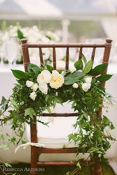 Green garlands and white roses add pretty to any chair.