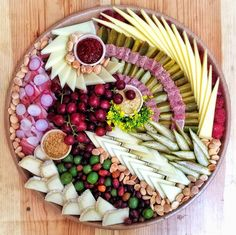 Cheese Platter: A variety of accompaniments is key, and this platter features Barrio Brinery pickles, dried Angelino plums, Rick's Picks Smokra, olives, grapes, radishes, mustard flowers, Marcona almonds, Heidi's Raspberry Jam, Lusty Monk Mustard, and Pommery honey mustard.