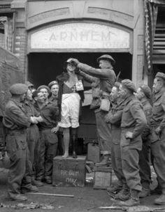 Lance-Corporal E.C. Crook of The Perth Regiment adjusting the hat of a mannequin, Arnhem, Netherlands, 15 April 1945.
