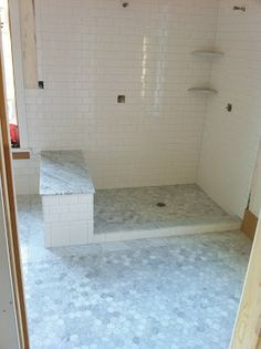 marble hex tile floors continued into the shower. white subway tile walls. marble slab bench.