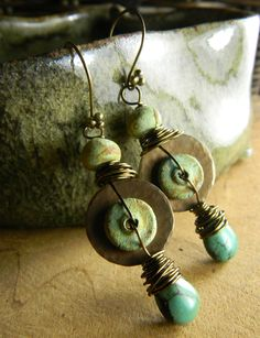 Rustic stone wear beads combined with turquoise drops and bronze for a striking tribal earring design with a distinctly tribal element. I have arranged the artisan stone wear beads with a hammered bronze disc and joined the components with bronze wire wrapping. The 4 ball bronze earwires finish the design perfectly. Total length of the earrings is 2.5 inches and they are slightly heavy in weight. Artisan stone wear beads from At Home in Taos on Etsy.