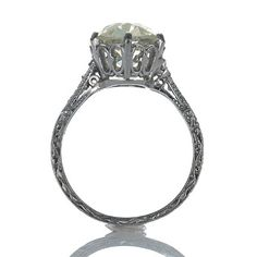 Stunning Edwardian engagement ring. A gorgeous Old Mine cushion cut diamond weighing 3.05 cts and certified by the GIA as UV color and VS2 clarity (Report #1142947032) has an enchanting pale yellow hue and phenomenal sparkle. Set with 6 round diamonds and beautifully hand engraved,this wonderful ring is a treasure from a bygone era. Platinum.