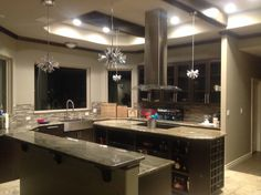 Octagon elongated island kitchen shape,,dark wood ceiling beams match the  lower cabinets. Not lit in this picture are the 4 radiant crystal fixtures that give subtle ambiant warm light in conjunction with or without other lights on in the kitchen.