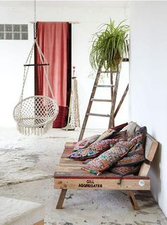 Up cycled crate day bed adorned with boho cushions. Ladder come shelving & crochet hammock pod. Perfect!