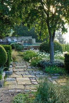 PROVENCE, FRANCE: GARDEN OF NICOLE DE VESIAN, LA LOUVE: SWIMMING POOL AT DAWN ON THE LOWER TERRACE WITH STONE PATH AND CLIPPED SHAPES AND COUNTRYSIDE (GARRIGUE) BEYOND