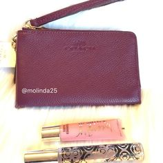 """Coach double Zip Wristlet clutch 100% Authentic Coach pebbled leather double zip wristlet/clutch. Fits iPhone 6  Color: Plum Strap drop 6""""  No trades or PP. Reasonable offers are welcome. MSRP: $150 Note: Lip gloss and perfume is not for sale. Just to show comparison for size. Coach Bags Clutches & Wristlets"""