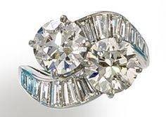 A diamond two-stone ring, Van Cleef & Arpels  of crossover design, centering two round brilliant-cut diamonds, weighing 2.07 and 2.18 carats, with baguette-cut diamond scrolling shoulders and a plain mount; signed VC SO 436; remaining diamonds weighing approximately: 1.00 carat total; mounted in platinum;