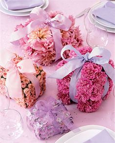 Unique floral centerpieces - petal presents - flower heads anchored in oasis and tied up with ribbon.