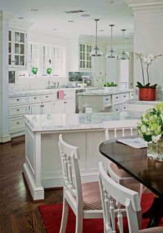 Antique chairs painted white to match cabinets, paired with dark wood dining table.