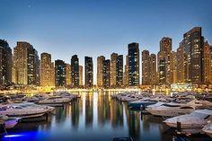 Dubai Marina, el puerto deportivo de Dubái↕ Mire hacia el futuro en el puerto deportivo artificial más grande del mundo, Dubai Marina. Maravíllese con algunos de los edificios más altos del planeta mientras que se pasea por Dubai Marina Walk o contempla la avenida desde el agua, surcando las olas desde el club de yates Dubai Marina Yatch Club