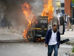 A man walks past a burning police vehicle, Monday, April 27, 2015, during unrest following the funeral of Freddie Gray in Baltimore. Gray died from spinal injuries about a week after he was arrested and transported in a Baltimore Police Department van.   Photo credit: AP / Patrick Semansky