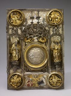 Cover of the Book of the Gospels made of silver; the draperies and the attributes of the applied figures are silver-gilt. Certain other details, like the wings of the angels, the frame mouldings of five roundels, together with the circle of fleur-de-lis cresting (in the centre), are also silver-gilt.[…]