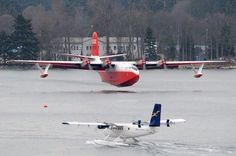 Martin Mars water bomber touching down, Twin Otter Taxiing in.  Vancouver Harbour, Canada. I get paid to fly one of them and dream about flying the other.