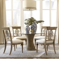 Tropical style radiates from this pedestal dining table with a 54-inch glass table top. The shaped pedestal features woven decoration complemented by carved top that is visible just below the glass. A decorative traditional splat elevates the classic look of the wood-back side chairs with upholstered seats.