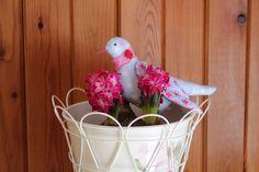 In liebevoller und aufwendiger Handarbeit genähter Vogel nach Tilda aus Baumwollstoff.  Der Halsschmuck besteht aus einem pinken Spitzenband und einer